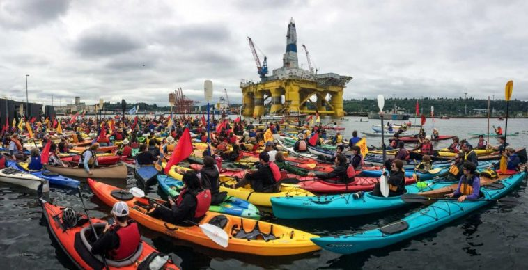 A crowd of kayaks on the water with shell's drilling rig looming in the background