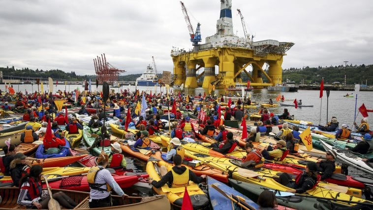 A mass of kayaks swarm in front of the Polar Pioneer drilling rig