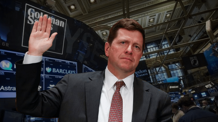 A photograph of Jay Clayton being sworn in to his confirmation hearing is superimposed over a background of Goldman Sachs and NY stock market images