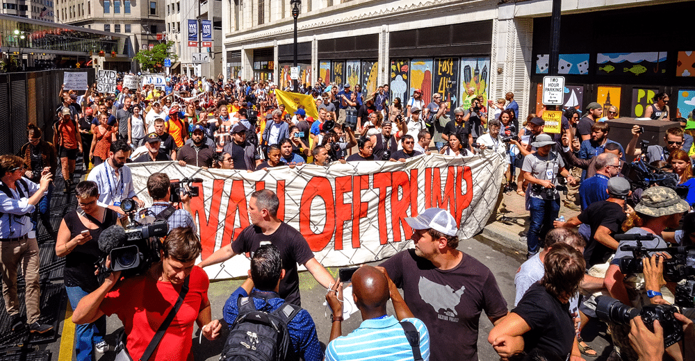 "An image of a large and colorful crowd. They're holding a banner that reads ""Wall Off Trump."" The crowd includes veterans, people with linked arms, and lots of people holding cameras, and appears to be a large protest."