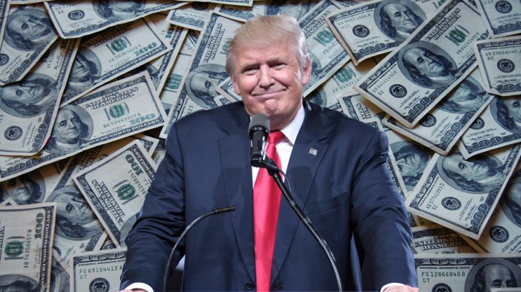 A photo of Donald Trump standing at a podium during a campaign rally is superimposed over a close-up image of many stacks of America $100 bills