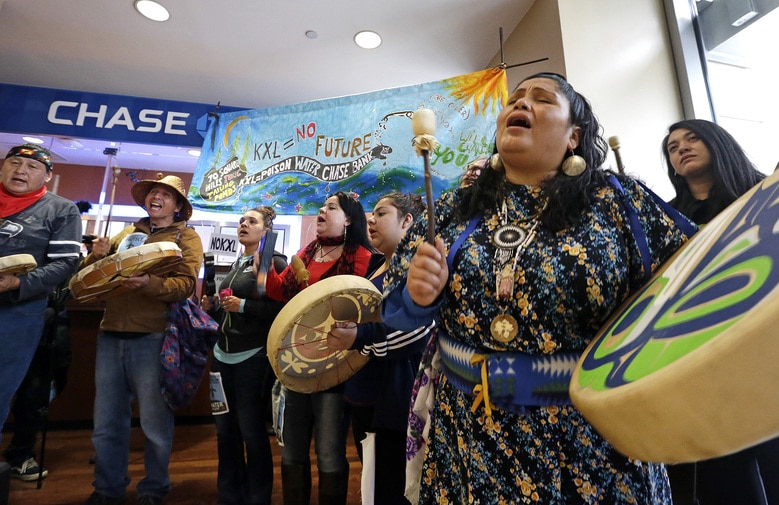 Roxanne White, a member of the Yakama Nation, sings during a Trans Mountain protest at a Chase branch