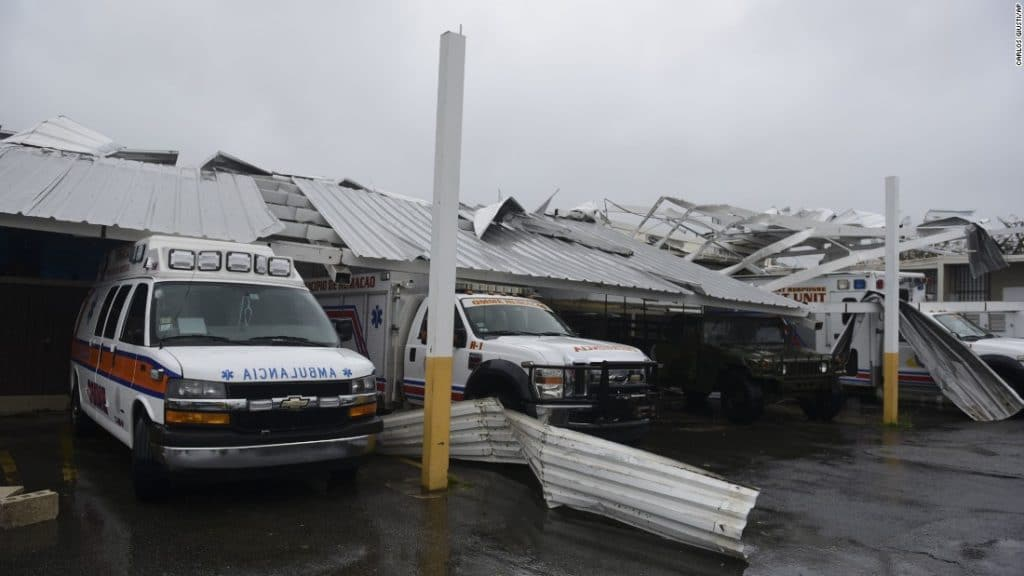 Rescue vehicles are trapped under an awning in Humacao