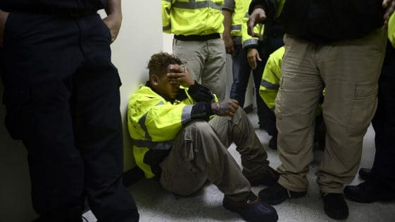 A rescue team member Jonathan Cruz cries on the floor in the aftermath of Hurricane Maria in Humacao, Puerto Rico; we can see the legs of his fellow rescue workers around him and he has his head in his hands