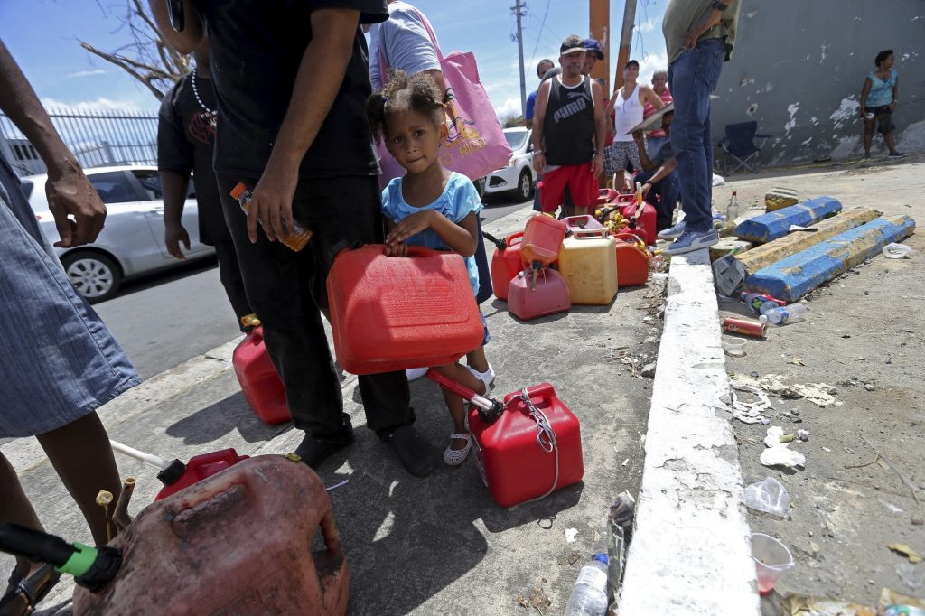 Abi de la Paz de la Cruz, 3, holds a gas can as she waits in line with her family, to get fuel from a gas station, in the aftermath of Hurricane Maria, in San Juan, Puerto Rico