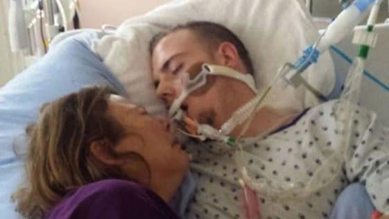 A woman lies with her dying son in a hospital bed. He is hooked up to feeding and breathing tubes.