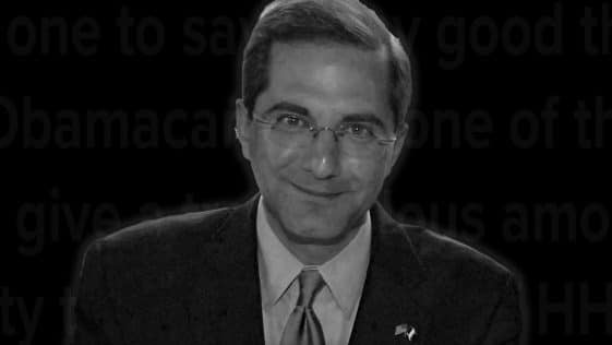 A black and white photograph of Alex Azar, from the chest up. He is wearing a suit and smiling for the camera. The background is black.