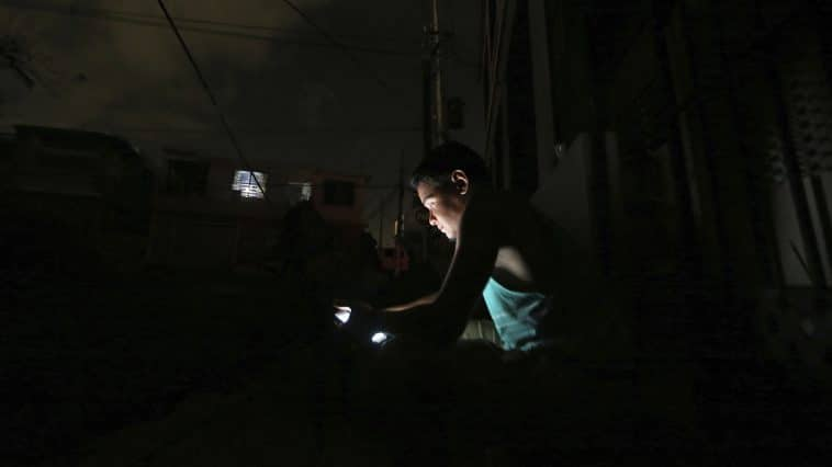 A very dark photo, but in the middle of the frame you can see a young man slightly lit up by the glow of a smart phone.