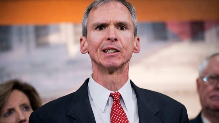 A photograph of Dan Lipinski from the chest up. He is wearing a red tie and making a weird face
