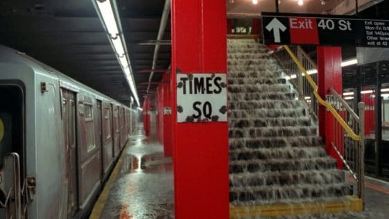 A photograph of the Times Square subway station in NYC. There is water pouring down a set of stairs in the middle of the photo, showing that the station is flooded.