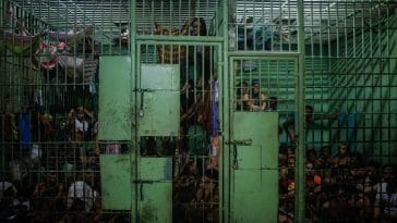A dark photograph of an overcrowded prison cell in the Philippines