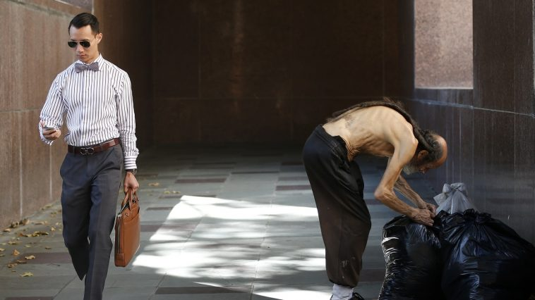 A man looks at his phone as he walks out of the courthouse past a man arranging his bags in Los Angeles, California July 8, 2014.