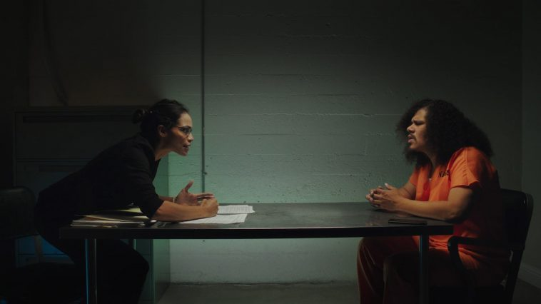 Two people sit across from eachother in a dimly lit interrogation room. One of them is wearing a bright orange jumpsuit.